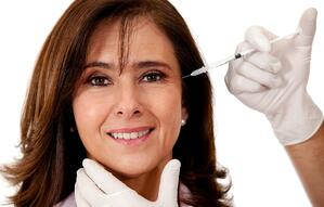 Woman getting a face lift with Botox - isolated over a white background